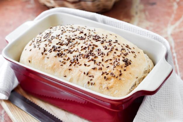 赤いセラミックのベーキング皿に亜麻の種子と自家製小麦パン