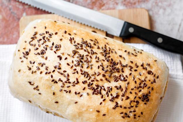 Домашний пшеничный хлеб с семенами льна на кухонном столе