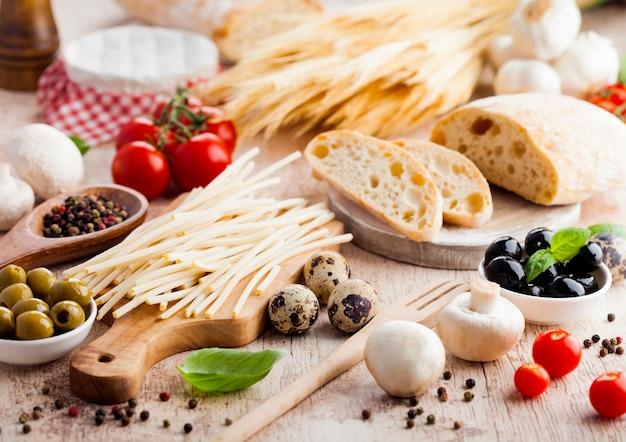 Домашний пшеничный хлеб с перепелиными яйцами и сырой пшеницы и свежих помидоров. классическая итальянская деревенская кухня. чеснок, маслины и оливки. деревянный шпатель