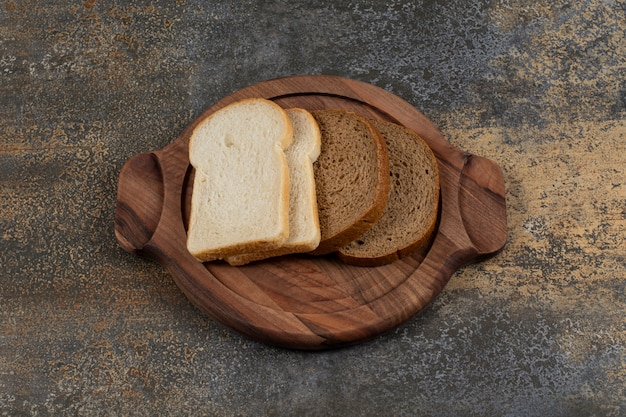 Homemade white and black bread slices on wooden board