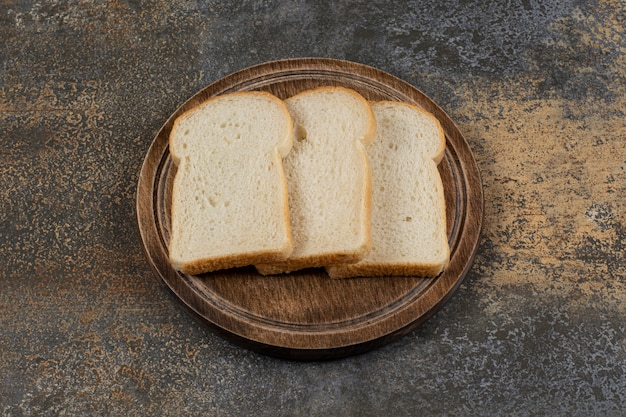 Homemade white bread slices on wooden board.