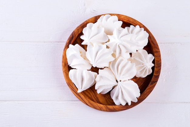 Homemade white meringue in wooden plate on white wood