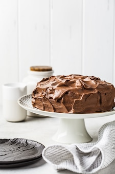 Homemade whole chocolate cake with chocolate cream and caramel on cake plate, white background.