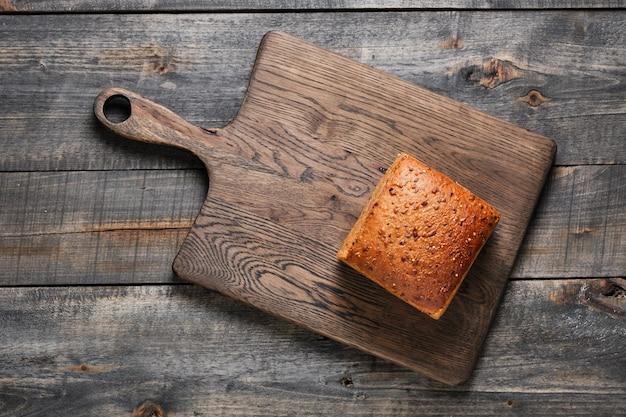 Домашний цельнозерновой хлеб на деревянном столе. здоровая выпечка.