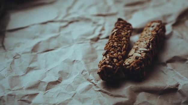 クラフト紙にオートミールとゴマの種が入った自家製全粒粉クッキー。食べ物の写真。レシピ本、コピースペース。健康的なビーガン全粒クッキー。