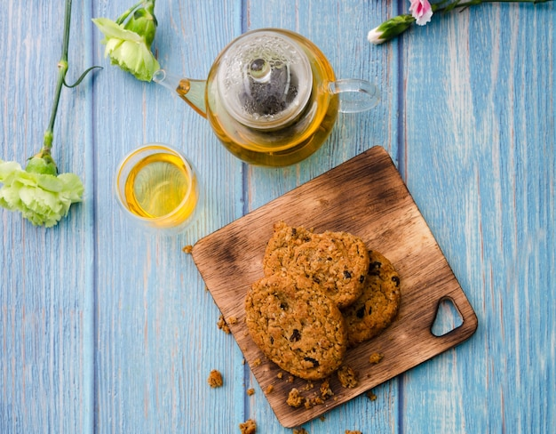 Homemade wholegrain cookies with raisin on wooden cutting board, a cup of tea, teapot and fresh flowers on blue wooden table, top view.