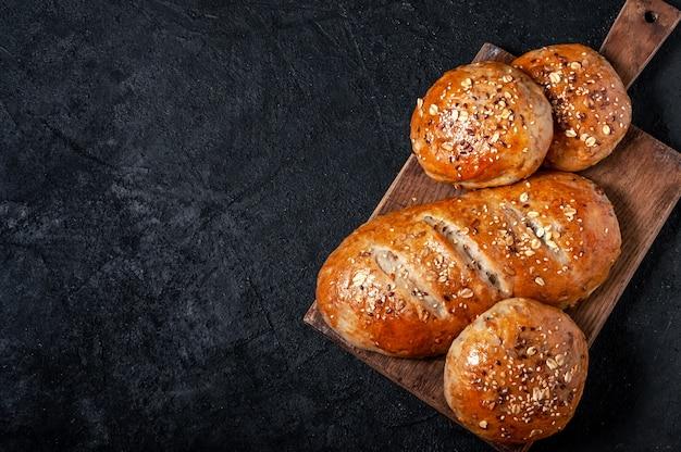 Домашний хлеб из цельнозерновой муки и булочки с семенами льна и кунжутом на темном столе. вид сверху плоская планировка. копировать пространство