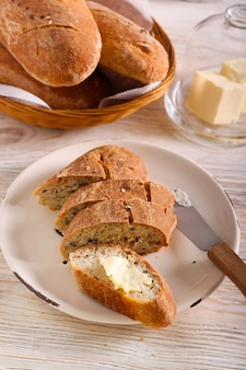 Homemade wholewheat mixed seed bread sliced and served with butter