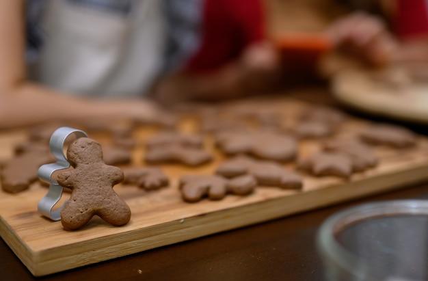 Домашнее рождественское печенье на рождество и новый год. женщина готовит пряники с другом и семьей на зимнем отдыхе дома.