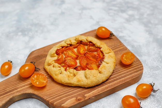 Homemade yellow cherry galette pie on grey light ,top view, for copy or text
