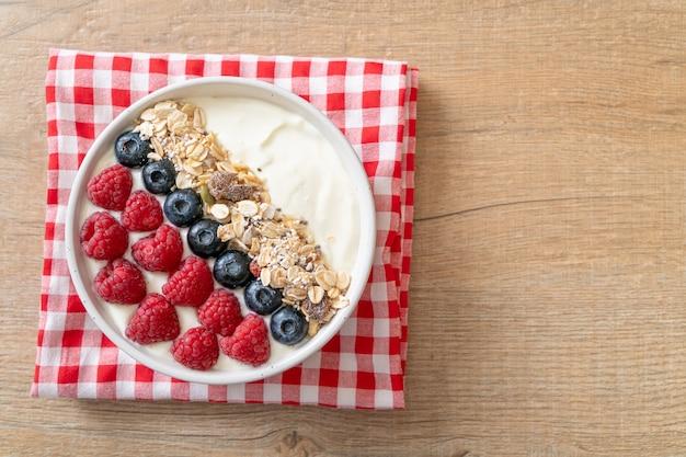 ラズベリー、ブルーベリー、グラノーラを使った自家製ヨーグルトボウル-健康的な食生活