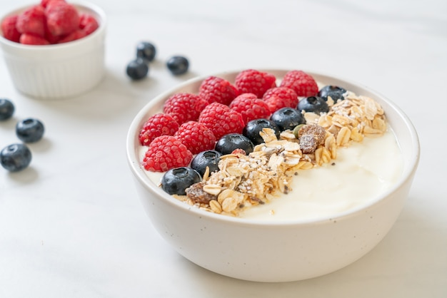 Homemade yogurt bowl with raspberry, blueberry and granola  - healthy food style