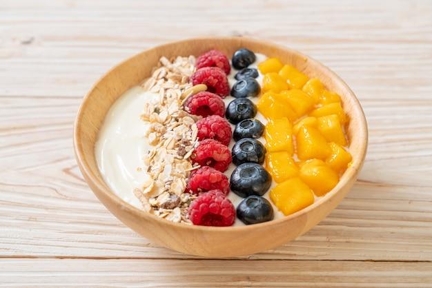 Homemade yogurt bowl with raspberry, blueberry, mango and granola - healthy food style