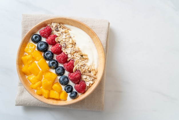 Homemade yogurt bowl with raspberry, blueberry, mango and granola - healthy food style