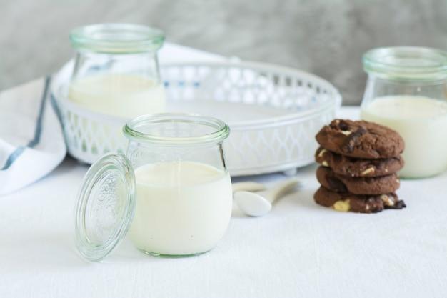 Homemade yogurt in a glass jars and chocolate cookies