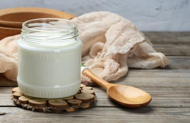 木製のテーブルの上のガラスの透明な瓶に入った自家製ヨーグルト、健康的な発酵乳製品