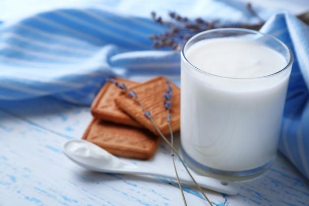 Домашний йогурт в стакане и вкусное печенье на деревянном столе
