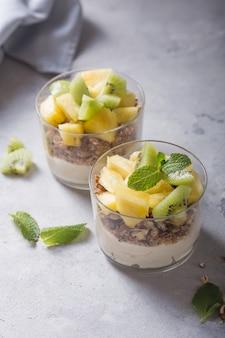 グラノーラ、キウイフルーツ、パイナップル、コンクリートの背景に健康的な朝食のガラスのナッツと自家製ヨーグルトパフェ