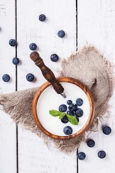 Homemade yogurt, sour cream in a wooden bowl
