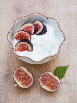 Домашний йогурт с инжиром и печеньем на деревянном столе