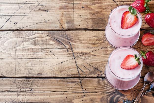 Домашний йогурт со свежей клубникой в очках на деревянном фоне. выборочный фокус. копировать пространство