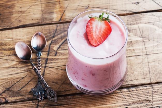Домашний йогурт со свежей клубникой в очках на деревянном. выборочный фокус. копировать пространство