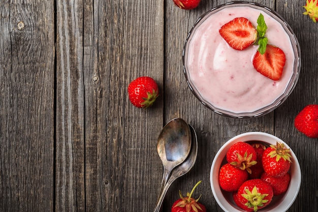 Homemade yogurt with fresh strawberry on a wooden