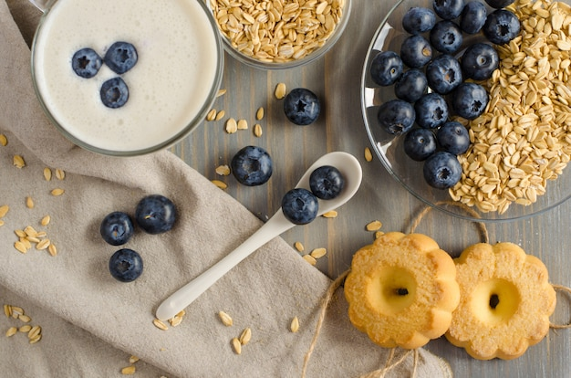 Homemade yogurt with oat groats and blueberries on pastel wooden table