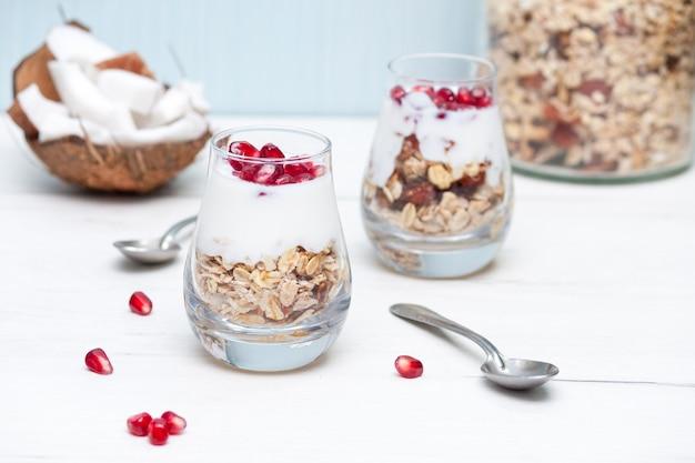 Домашний yougurt с мюсли и плоды граната в очках на белом деревянном столе. здоровый завтрак.