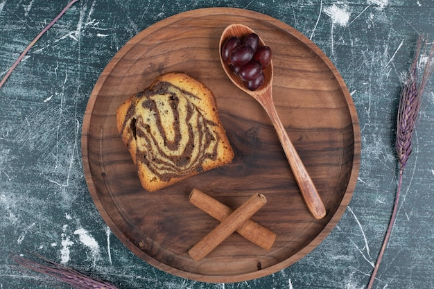 Torta zebrata fatta in casa su piatto di legno con cannella e uva.