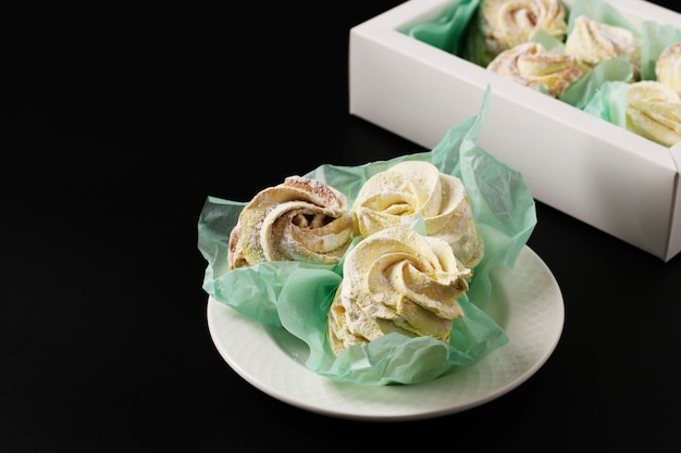 Homemade zephyr and marshmallows in a box on a dark background, horizontal orientation, closeup