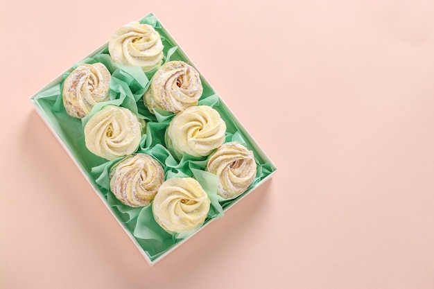 Homemade zephyr or marshmallows in a box on a pink background, horizontal orientation, top view