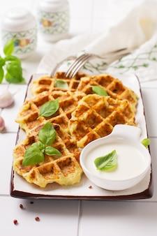 白い背景にチーズ、ソース、葉のバジルと自家製ズッキーニワッフル。ケトダイエット食品のコンセプト。