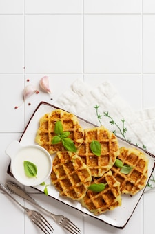 Homemade  zucchini waffles with cheese,sause and leaf basil on white  table. concept of keto diet food. selective focus.