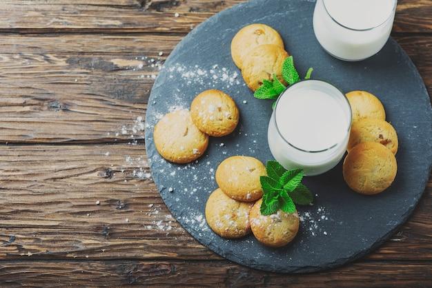 木製のテーブルに牛乳とホームミードクッキー