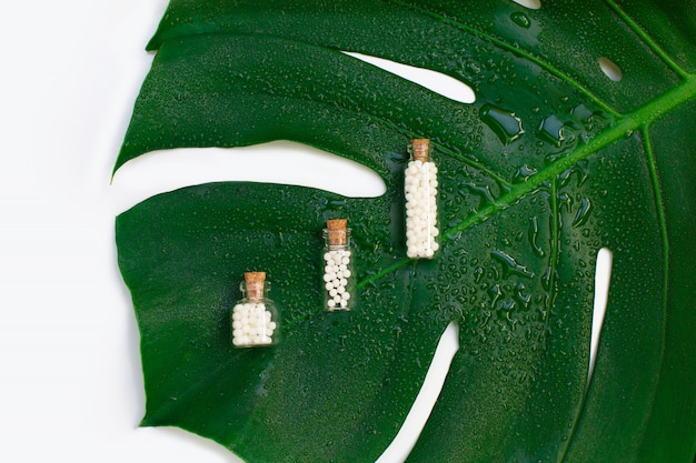 Homeopathic globules in three glass bottles on wet palm leaf background.