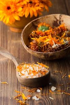 Гомеопатическое лекарство, сухие цветы календулы и деревянная поверхность.