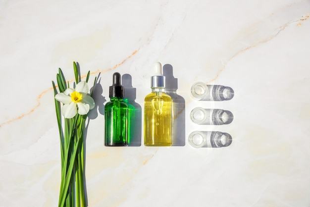 대리석에 식물이 있는 동종요법 오일, 혈청, 병. 천연 유기농 화장품