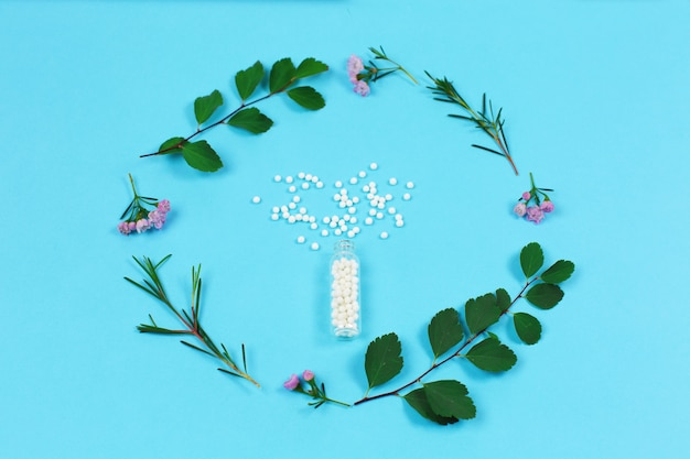 Homeopathic pills and green plant leaves