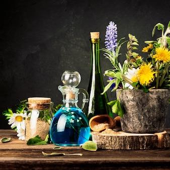 ホメオパシーと代替医療。石乳鉢の癒しのハーブとガラス瓶のエッセンシャルオイル。木製のテーブルに癒しのハーブを粉砕しました。