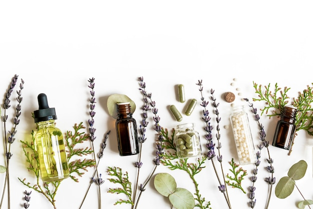 Homeopathy eco alternative medicine concept - classical homeopathy pills, thuja, eucalyptus, lavender essential and aroma oil and healing herbs and on white wall. flatlay. top view. copyspace