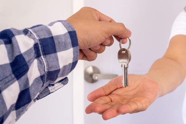 Homeowner or sales representative giving the keys to the hand of the tenant.
