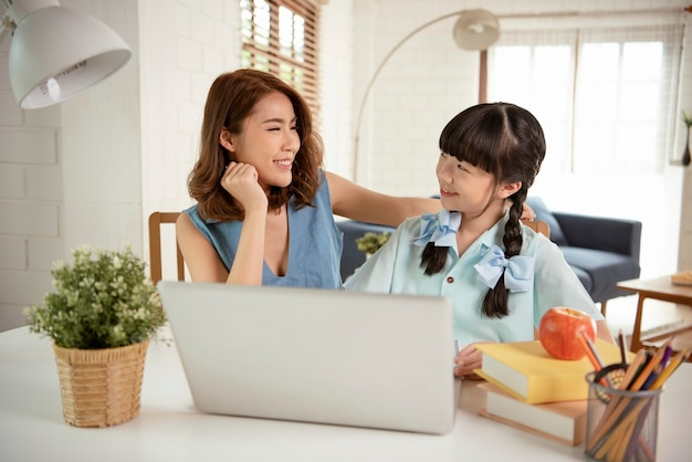ホームスクーリングアジアの小さな女の子の学生は、自宅で家庭教師と一緒にテーブルに座って学習しています。