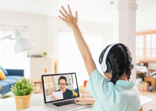 Homeschool азиатский студент маленькой девочки изучает виртуальный интернет-класс онлайн на столе у себя дома. концепция дистанционного онлайн-обучения. защитить от вирусов covid-19.
