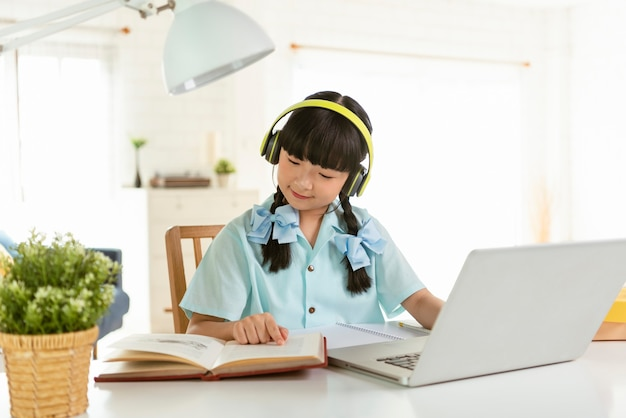 Homeschool asian little young girl student learning virtual internet online class on table at home.