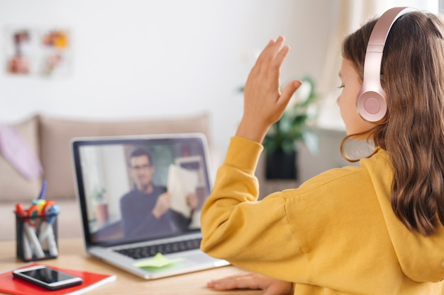 Homeschool little young girl learning virtual internet online class from school teacher by remote meeting due to covid pandemic