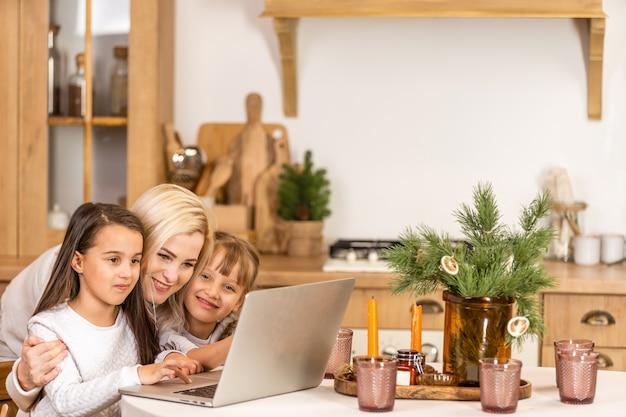 홈스쿨. 어린 두 딸이 온라인으로 인터넷을 배우고, 어머니의 도움으로 컴퓨터를 사용하여 숙제를 하고, 가르치고 격려합니다. 집에서 함께 교육을 공부하다
