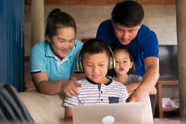 Homeschooling child boy in headphone using laptop computer with happy asian family togetherness in rural home, parents helping kid with homework during covid-19 pandemic.