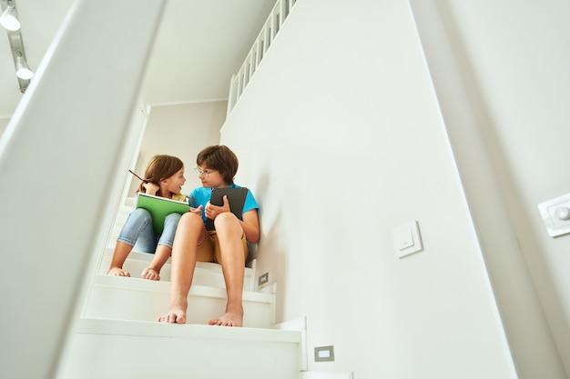 デジタルタブレットを使用して自宅の階段に座っているホームスクーリングのコンセプト弟と妹と
