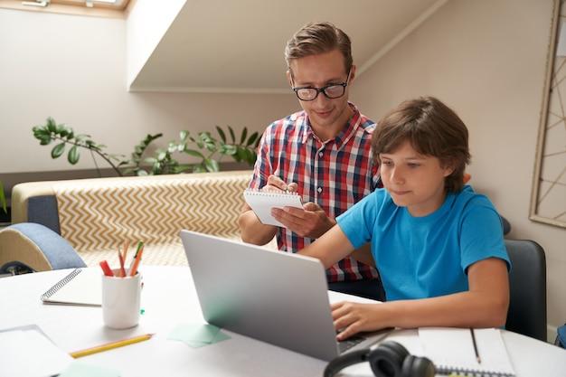 Концепция домашнего обучения молодой отец в очках и его маленький сын смотрят видеоурок